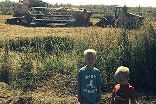 Family photo in front of Battle River Wild Rice equipment on the farm